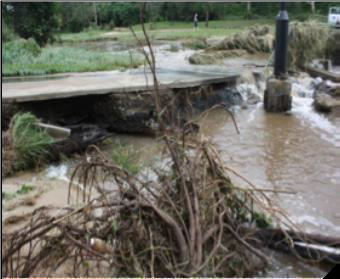 A concrete river ford shown side-on. One end of the ford has collapsed into the river.