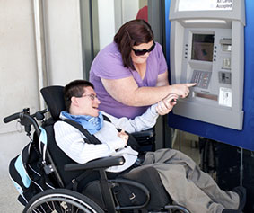 Carer and man in wheelchair use an ATM.
