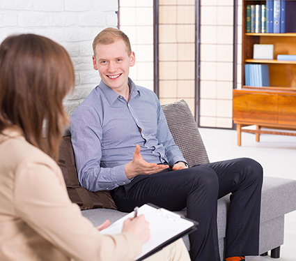 Young man speaking with psychologist