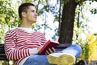 Photograph of a young man sitting alone outside, reading a book.