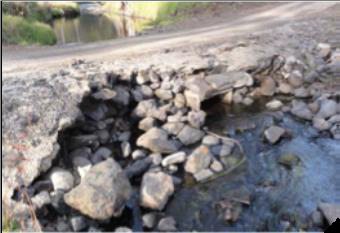River crossing shown side-on. The road surface has been undercut.