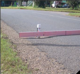 Close-up of asphalt road. A straight rod has been put down to show the depth of the ruts in the road.