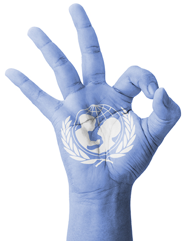 A hand, painted United Nations blue with the logo on the palm, makes an A-OK sign