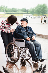 A man in a wheelchair laughs at something his companion has said