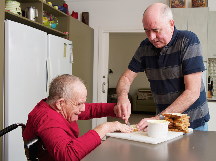 A carer interacts with a man with disability.