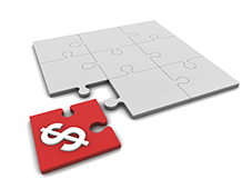 A red piece of a jigsaw puzzle, with a dollar sign on it, is about to fit into the rest of the puzzle, which is grey