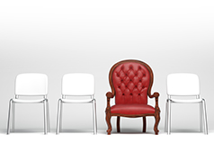 A fancy red leather armchair stands out from among three plain white plastic seats