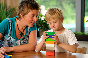 Teacher with a small child using building blocks