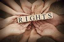 The word 'rights' is spelled out in Scrabble letters, resting on a circular cluster of hands