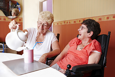 A woman with disability enjoys the company of her carer, who is pouring her a cup of tea.