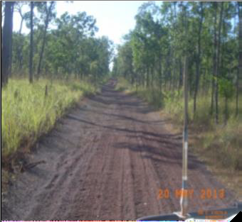 Dirt road extends from the viewer's feet directly to the horizon. The road surface is deeply rutted.
