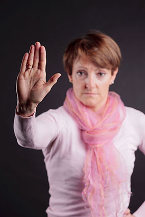 A woman holds up her hand, indicating 'Stop!'.