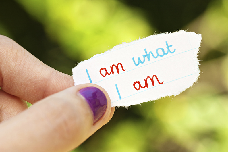 A woman's hand holds a torn scrap of paper, on which is written the words: I am what I am.