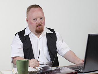Working man with Down syndrome at his desk