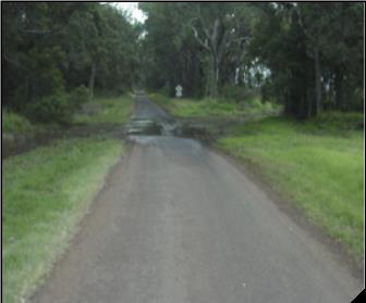 Asphalt road extends from the viewer's feet and extends directly away. In the middle distance is a floodway. There is some water over the road at the floodway.